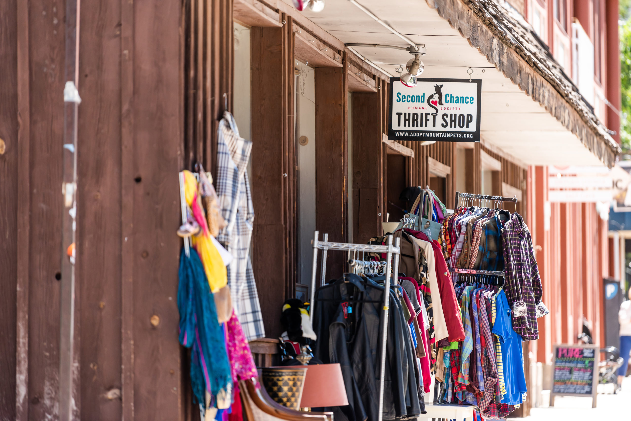 Telluride, USA - August 14, 2019: Vacation town village in Colorado with sidewalk and sign for second chance hand thrift store shop with clothes on rack display